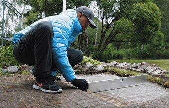 Hohteen työntekijä korjaa pihakivetyksen kaatoa