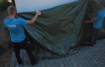 Hohteen työntekijät peittämässä seinää suojakankaalla